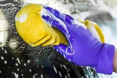 Мужские руки в перчатках, мойке с желтой губкой Стоковые Фотографии RF