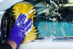 Мужские руки в перчатках, мойке с желтой губкой Стоковое фото RF