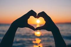 Мужские руки в форме сердца на заходе солнца Стоковые Фото
