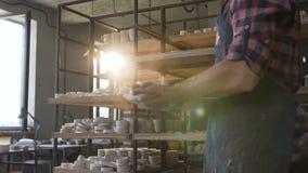 Мужские руки гончара хлопая в ладоши на предпосылке гончарни солнечного света акции видеоматериалы