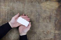 Мужские руки держа белый чистый лист бумаги Стоковое Изображение RF