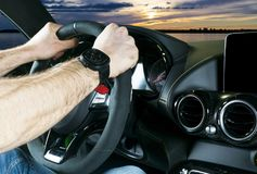Мужские руки держа рулевое колесо автомобиля Руки на oMale рулевого колеса вручают держать рулевое колесо автомобиля Руки на руле Стоковое Фото