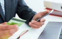 Мужские руки держа умные телефон и кредитную карточку на офисе Дело, технология, получает наличными свободно и концепция людей ин стоковые фотографии rf