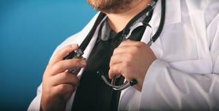 Мужские руки доктора therapeutist медицины держа стетоскоп на его комоде в крупном плане руки Врач ждет пациента стоковые фотографии rf