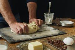 Мужские руки замешивают тесто варя кухню перекрестных плюшек домой Стоковая Фотография