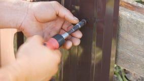 Мужские руки исправляют загородка с особенными винтами и ручной отверткой сток-видео