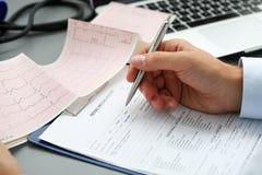 Мужские руки доктора с диаграммой cardiogram на пусковой площадке доски сзажимом для бумаги Стоковые Фото