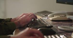 Мужские руки печатая на клавиатуре компьютера и касаясь мыши