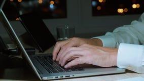 Мужские руки печатая текст на клавиатуре тетради пока программирующ в темном офисе акции видеоматериалы