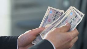 Мужские руки подсчитывая деньги, обменивая японские иены на отделении банка, финансы сток-видео