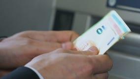 Мужские руки подсчитывая евро приближают к ATM и деньги установки в бумажнике, банке, крупном плане видеоматериал