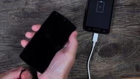 Мужские руки прикрепляют умные телефоны к проводам заряжателя сток-видео