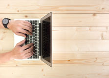 Мужские руки работая на компьтер-книжке на деревянном настольном компьютере Стоковое Изображение
