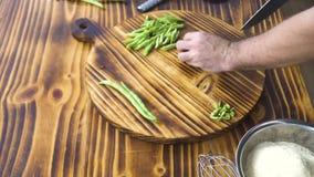 Мужские руки режа зеленые фасоли с ножом Отслеживать снятого повара отрезая зеленые фасоли на деревянном столе Вырезывание взгляд акции видеоматериалы
