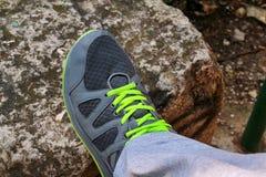 Мужские руки связывая вверх по шнуркам на идущей тапке, конец вверх Часть спортсмена связывая тапки Нога на утесе Стоковые Изображения RF