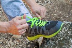 Мужские руки связывая вверх по шнуркам на идущей тапке, конец вверх Часть спортсмена связывая тапки Нога на утесе Стоковые Фото