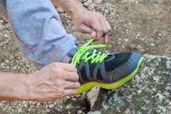 Мужские руки связывая вверх по шнуркам на идущей тапке, конец вверх Часть спортсмена связывая тапки Нога на утесе Стоковое фото RF