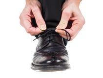 Мужские руки связывая шнурки на черных кожаных ботинках Стоковое Фото