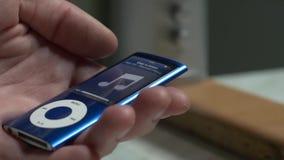 Мужские руки соединяют наушники к iPod, аудиоплейеру, mp3 плэйер Пары наушников в руке женщины самомоднейше сток-видео