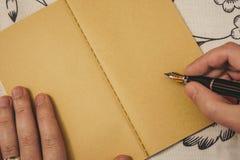 Мужские руки с сочинительством обручального кольца с авторучкой на тетради kraft Особенное событие или случай с космосом экземпля стоковое фото