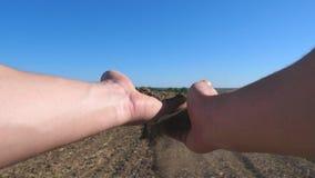 Мужские руки фермера держа кучу сухой почвы и лить ее назад через его пальцы на поле на солнечном дне Концепция сток-видео