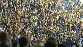 Мужские сторонники хлопать, веселящ для национальной футбольной команды на стадионе акции видеоматериалы
