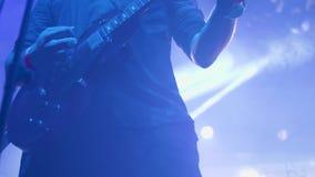 Мужские утесы музыканта на гитаре перед толпой на рок-концерте акции видеоматериалы