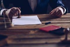 Мужские юрист или нотариус штемпелюя документ в его в офисе Стоковые Изображения