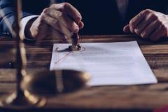 Мужские юрист или нотариус штемпелюя документ в его в офисе Стоковая Фотография