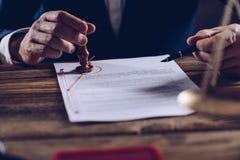 Мужские юрист или нотариус штемпелюя документ на его офисе Стоковое фото RF