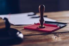 Мужские юрист или нотариус штемпелюя документ на его офисе Стоковые Фото