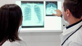 Мужские explaines доктора что-то на рентгеновском снимке к его женскому коллеге акции видеоматериалы