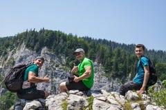 Мужские hikers на скале горы Стоковая Фотография