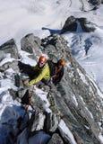 2 мужских альпиниста на крутом гребне утеса и снега в швейцарских Альпах Стоковое Изображение RF