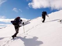 2 мужских альпиниста с тяжелыми рюкзаками на пути к саммиту на зимний день Стоковая Фотография