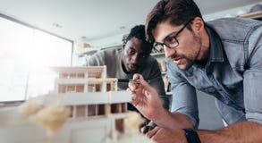 2 мужских архитектора обсуждая над моделью дома Стоковая Фотография