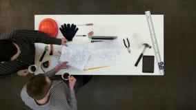 2 мужских архитектора обсуждая светокопии выпивая кофе сток-видео