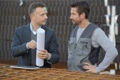 2 мужских архитектора обсуждая светокопию outdoors Стоковые Фотографии RF
