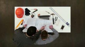 2 мужских архитектора обсуждая чертежи и светокопии видеоматериал