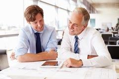 2 мужских архитектора работая совместно на столе в офисе Стоковая Фотография RF