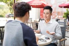 2 мужских бизнесмена сидя в кафе и обсуждая дело pro Стоковая Фотография