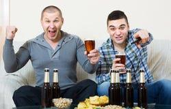 2 мужских болельщика наблюдая игру дома Стоковые Фото