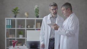 2 мужских доктора проверяя информацию на планшете, обсуждая Концепция медицины, технологии, здравоохранения и людей видеоматериал