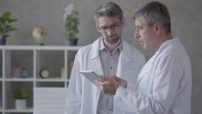 2 мужских доктора проверяя информацию на планшете, обсуждая Концепция медицины, технологии, здравоохранения и людей сток-видео