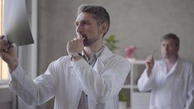 2 мужских доктора проверяя рентгеновский снимок в офисе современной клиники Более молодой человек в белом рентгеновском снимке по видеоматериал