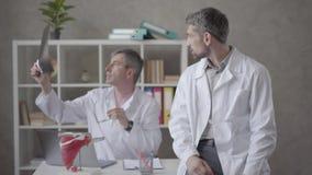 2 мужских доктора проверяя рентгеновский снимок в офисе современной клиники Более молодой человек в рентгеновском снимке показа р видеоматериал