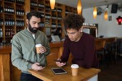 2 мужских друз используя мобильный телефон пока имеющ кофе Стоковая Фотография
