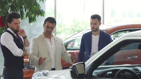 3 мужских друз рассматривая автомобиль для продажи на дилерских полномочиях видеоматериал