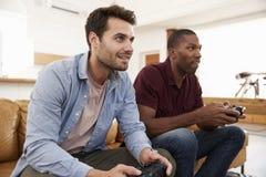 2 мужских друз сидя на софе в салоне играя видеоигру Стоковые Изображения