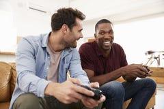 2 мужских друз сидя на софе в салоне играя видеоигру Стоковые Изображения RF